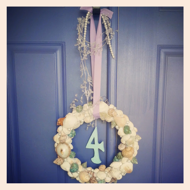 a mermaid wreath covered in seashells hanging on a blue door
