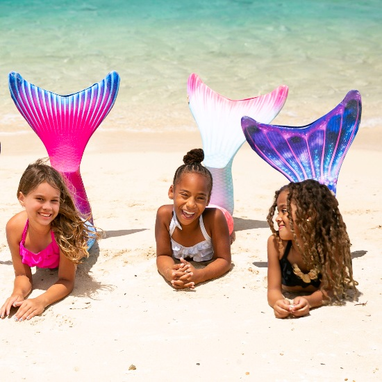 three mermaids on the beach wearing three different Limited Edition mermaid tails