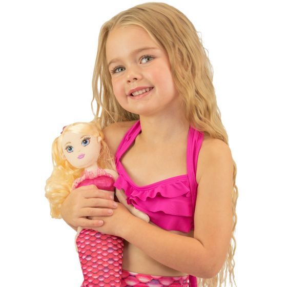 A young girl holds the Waverlee Mermaidens doll wearing matching pink scales.