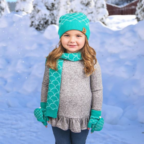 A girl wearing the hat, mitten, and scarf set stands in front of a snowy background.