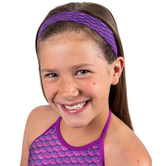 A smiling girl wears the Asian Magenta purple scale headband.