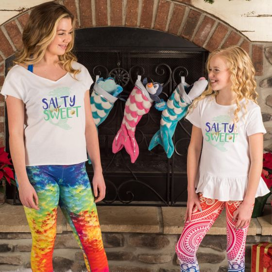 Two girls stand in front of mermaid stockings.