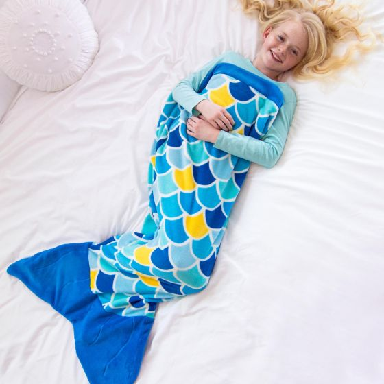 A girl lays on a bed in a blue mermaid tail blanket.