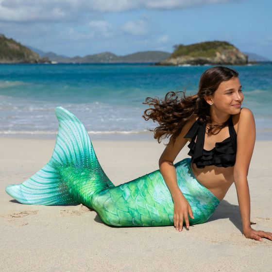 A girl poses on the shore in a mermaid tail with green and aqua scales.