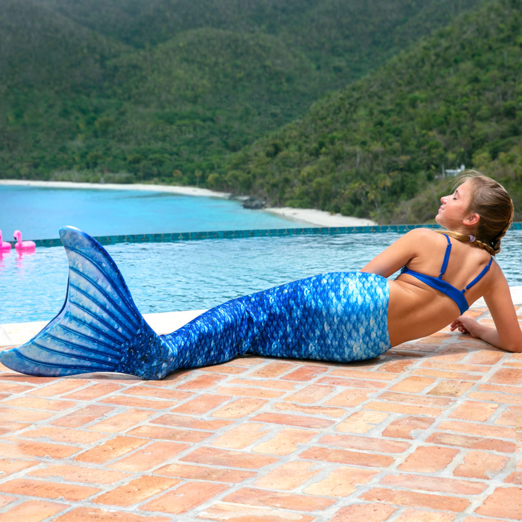 A girl lays poolside in a blue mermaid tail.