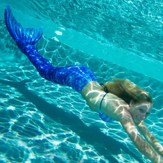 A girl smiling underwater wearing a royal blue swimmable mermaid tail.