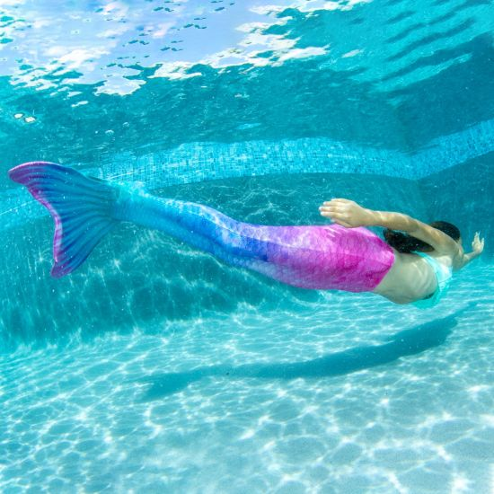 A girl swims underwater in the pink and blue Fiji Fantasy mermaid tail.