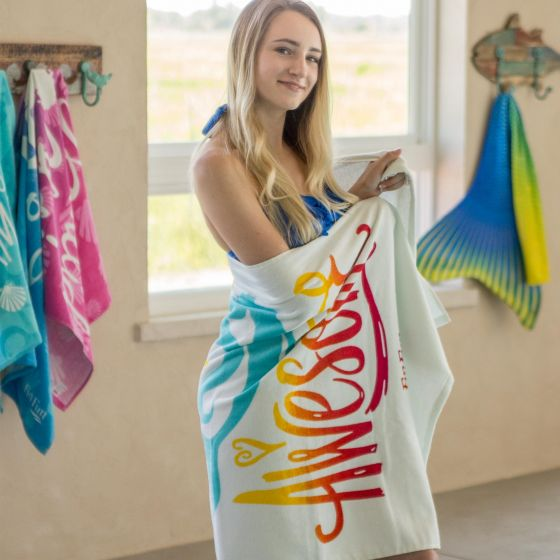 A girl wrapped in a mermaid beach towel stands by the pool.