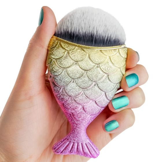 A hand with teal nail polish holds a gold and pink mermaid makeup brush.