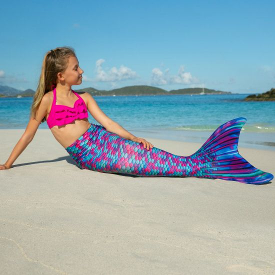 A young girl sits in the sand in a mermaid tail with berry-colored scales.