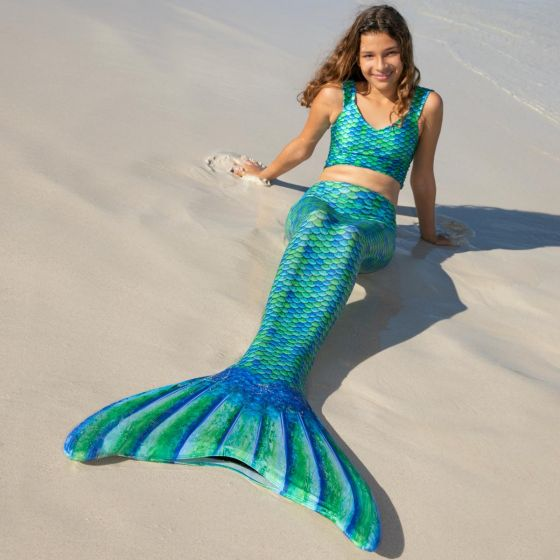 A girl lays in the sand wearing a blue and green-scaled mermaid tail and crop top.