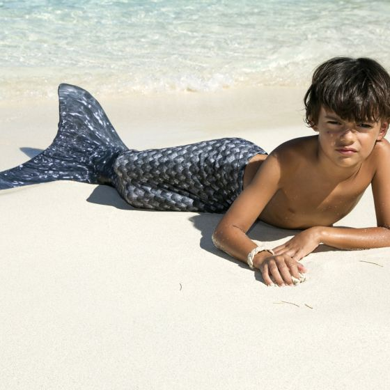 A boy lays in the sand wearing the Barracuda Black merman tail.
