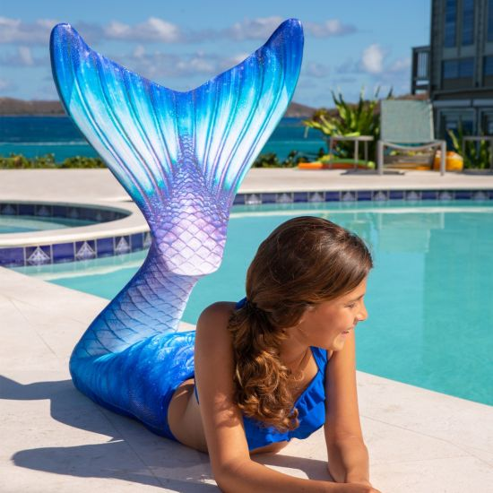 A girl lays next to the pool in a blue bikini top and blue, white, and purple mermaid tail.
