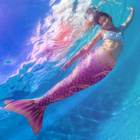 a girl swimming underwater in the pink and yellow Deep Sea Rave Limited Edition tail
