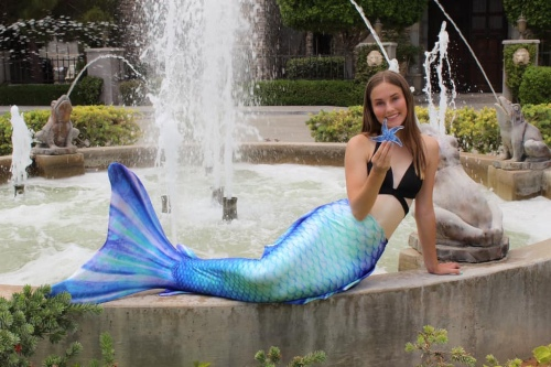 Mermaid Kylie posing by a fountain while wearing the Pacific Pearl Altantis mermaid tail.