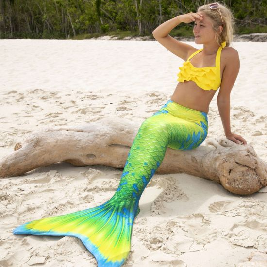 A girl sits on a log while wearing a yellow, green, and blue mermaid tail, a yellow bikini top, and sunglasses.