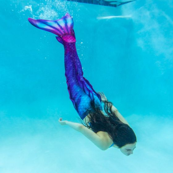 a girls dives underwater in a blue and pink mermaid tail that has side, ankle, and dorsal fins