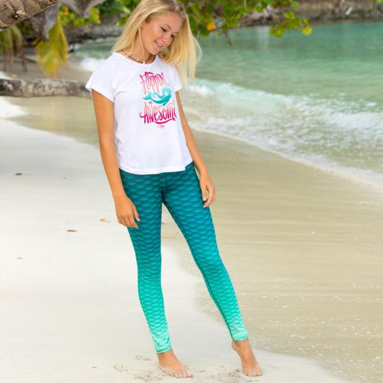 """a girl stands on the beach wearing green ombre leggings and a white shirt that say """"flippin' awesome"""" around a mermaid silhouette"""
