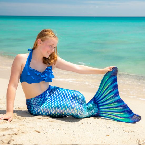 a girls sits in the sand while wearing a blue, green, and white mermaid tail