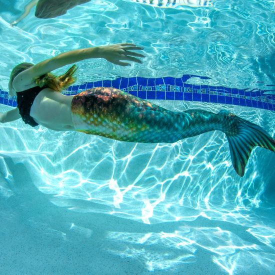 a girl swimming underwater in a green and bronze mermaid tail