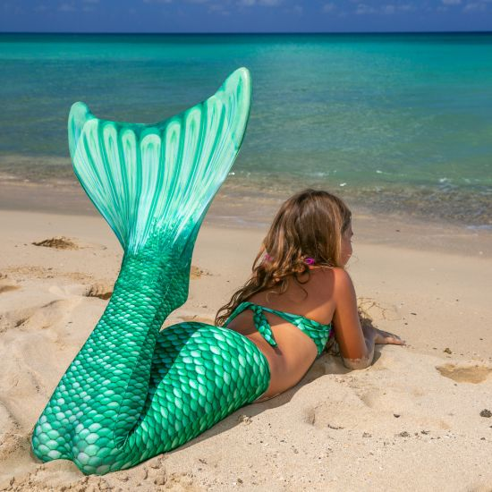 a young mermaid lays on the beach in a green mermaid tail