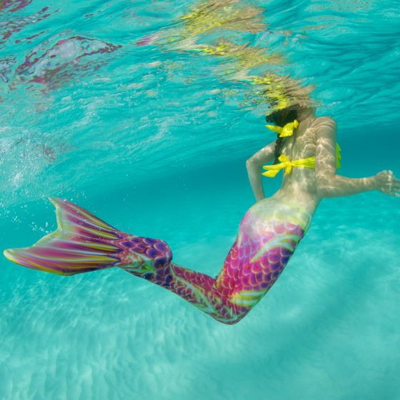 an underwater shot of a mermaid swimming underwater in a pink and gold mermaid tail