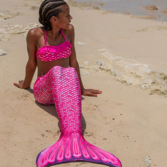 a young mermaid sitting on the beach in a pink mermaid tail