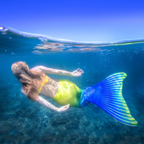 an underwater shot of a mermaid swimming in a yellow and blue mermaid tail