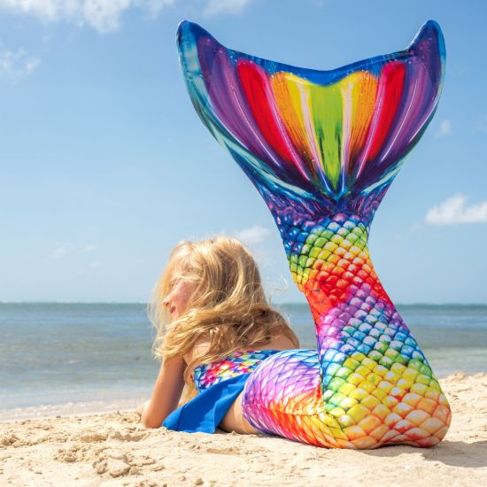 a mermaid laying on the beach in a rainbow mermaid tail