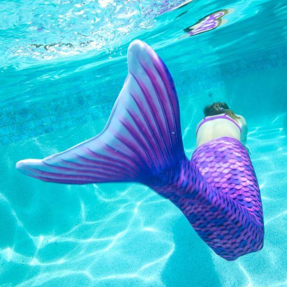 a mermaid swimming underwater in a purple mermaid tail