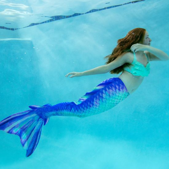 a magical underwater shot of a mermaid in a mermaid tail with side fins