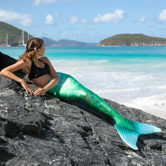 a girl lays on a rocky surface in a green mermaid tail with the ocean in the background